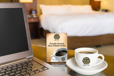 Cup of New Orleans Roast coffee next to laptop in hotel